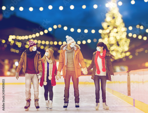 friendship, christmas and leisure concept - friends wearing face protective medical masks for protection from virus disease holding hands at outdoor skating rink over holiday lights background