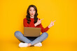 Photo of attractive shocked lady sit floor legs crossed work computer remote worker education home direct fingers empty space wear casual outfit isolated yellow color background