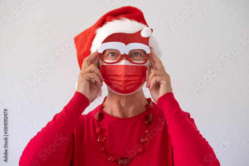 Fotomural A senior woman dressed in red as Santa Claus wearing a surgical mask due to the coronavirus and a pair of witty glasses