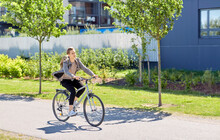 Lifestyle, Transport And People Concept - Young Man Or Teenage Boy With Backpack Riding Bicycle On City Street