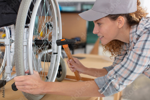 Obraz woman making an adjustment on a wheelchair - fototapety do salonu