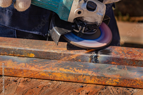 A worker in overalls is grinding a weld seam on a steel square profile pipe with Wallpaper Mural