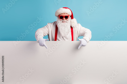 Portrait of his he nice attractive funky confident cool white-haired Santa demonstrating copy space board advice recommend look idea isolated over bright vivid shine vibrant blue color background - 384109210