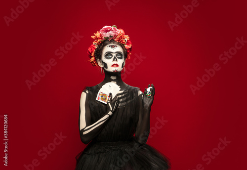 Gambling. Young girl like Santa Muerte Saint death or Sugar skull with bright make-up. Portrait isolated on red studio background with copyspace. Celebrating Halloween or Day of the dead.
