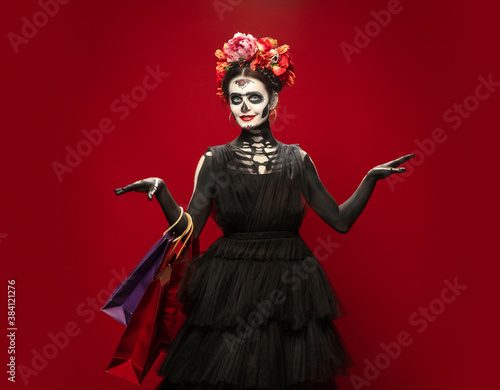 Shopping. Young girl like Santa Muerte Saint death or Sugar skull with bright make-up. Portrait isolated on red studio background with copyspace. Celebrating Halloween or Day of the dead. Black friday