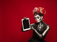 Holding Tablet. Young Girl Like Santa Muerte Saint Death Or Sugar Skull With Bright Make-up. Portrait Isolated On Red Studio Background. Celebrating Halloween Or Day Of The Dead. Copyspace On Screen.