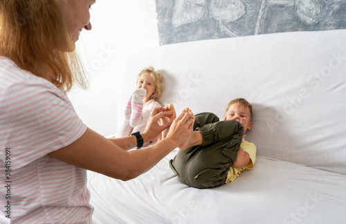 Mom tickles the little boy's feet. The boy laughs. Canvas-taulu