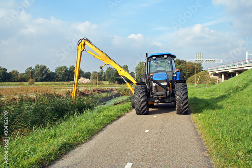 Obraz Summer ditch cleaning by a tractor in  a Dutch polder ;andscape - fototapety do salonu