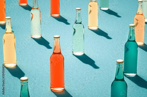 Fototapeta Various color glass bottles with shadows on blue surface. obraz