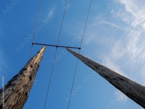 Fotografia View on wooden electric pole against deep blue cloudy sky
