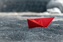 Red Paper Boat In Black Sand O...
