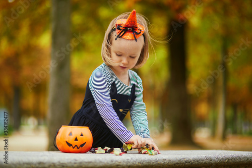 Adorable toddler girl in black cat dress with tutu skirt trick-or-treating with orange pumpkin bucket