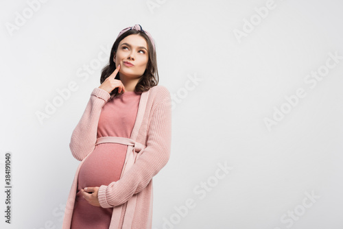 Canvas-taulu pensive pregnant woman in headband touching face and looking up isolated on whit