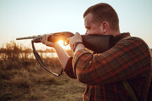 Young Irish Looking Man With A Reed, Backpack And Ammunition Belt,  Hunting At The Countryside Near The Track In The Picturesque Sunset Rays - Photo With Selective Focus