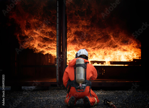 Fotografia Firefighter with uniform and helmet stand, High pressure water lance quenches fires Temperature and time - the twoTs - are crucial elements to stopping fires