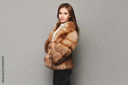 Fotografie, Obraz Side view of a model girl in a luxurious fur coat at the grey background