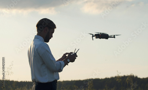 Side view of man holding remote controller navigating quadcopter hovering in air Fototapet