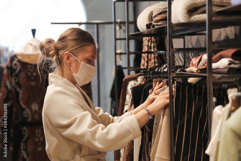 Fototapeta  woman with mask chooses clothes inside a shop