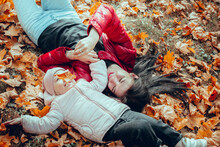 Mom And Daughter Lie On Fallen Leaves