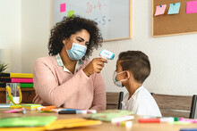 Teacher Woman Checkup Temperature On Child In Classroom During Corona Virus Pandemic - Healthcare Medical And Education Concept