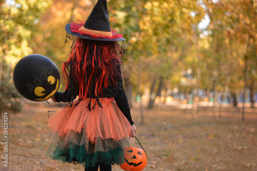 Little girl in witch costume with a balloon and a pumpkin bucket playing in autumn park. Child having fun at Halloween trick or treat. Kids trick or treating.