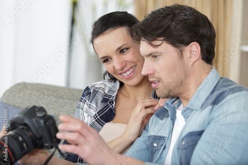 affectionate young couple relaxing together on a sofa checking photographs Canvas Print