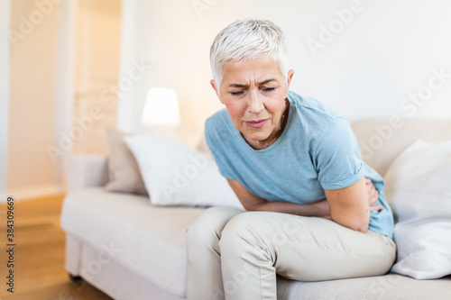 Fotografie, Obraz Middle-aged woman sitting on bed feels unhealthy touch stomach suffers from seve