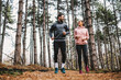 canvas print picture - Full length of fit couple running trough woods at autumn and preparing for marathon.