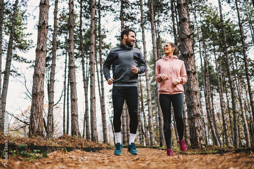 Full length of fit couple running trough woods at autumn and preparing for marathon. - 384316848
