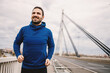 canvas print picture Smiling fit sportsman in tracksuit running on the bridge at cloudy weather and preparing for marathon. Healthy lifestyle concept.