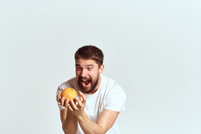 A Man With An Orange In A Whit...