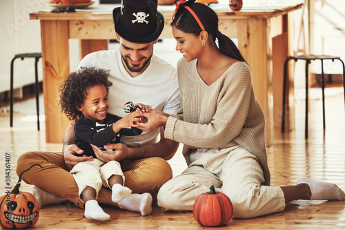 happy multiethnic family mom, dad and son have fun and celebrate Halloween at home.