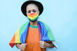 Portrait of gay young woman with mask wearing a rainbow flag - Lgbt concept - Focus on face