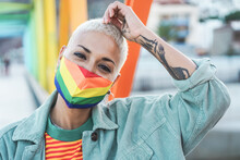Portrait Of Gay Woman Wearing A LGBT Rainbow Flag Mask - Focus On Girl's Face