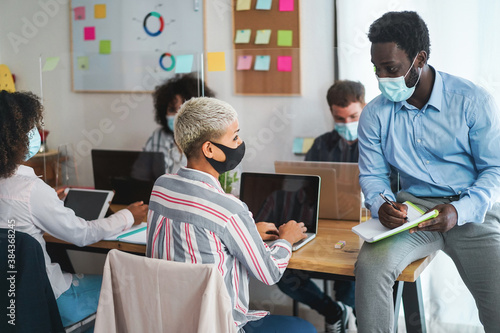 Obraz Multiracial young people with face masks in modern coworking office wearing protective masks for coronavirus spread prevention - Startup and social distance concept - Focus on man's face - fototapety do salonu