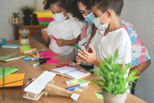 School teacher helping children in classroom while wearing safety masks  during coronavirus outbreak- Focus on boy's face - 384368286