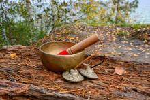 Himalayan Tibetan Singing Bowl Yoga Bowl With Stick And Tibetan  Bells,Cymbal, Karatals, Tingsha  On Wood In Autumn Background. Meditation With Singing Bowl.