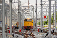 Thai Local Old Classic Train Or Tram On Railway With Utility Poles Tower And Cable Wires In Terminal Station In Urban City In Public Transportation, Energy Electric Technology And Industry Concept.