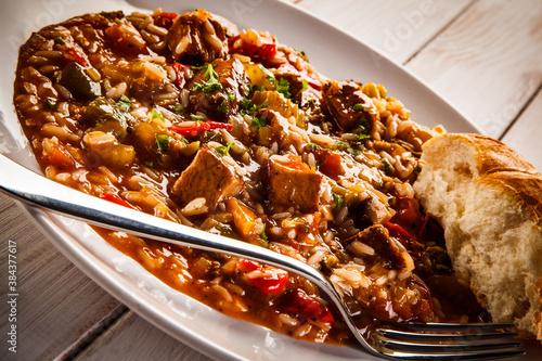 Roast pork meat with rice and vegetables on wooden background © Jacek Chabraszewski