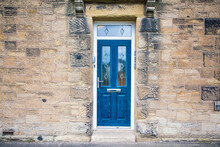 Blue Door Building With Traditional Silver Handles And Glass Windows In Stone Build House