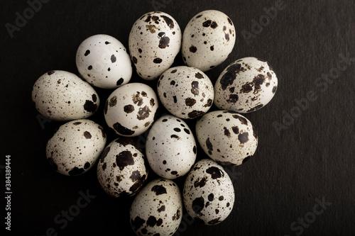 fresh quail eggs on a black background. Top view Wallpaper Mural