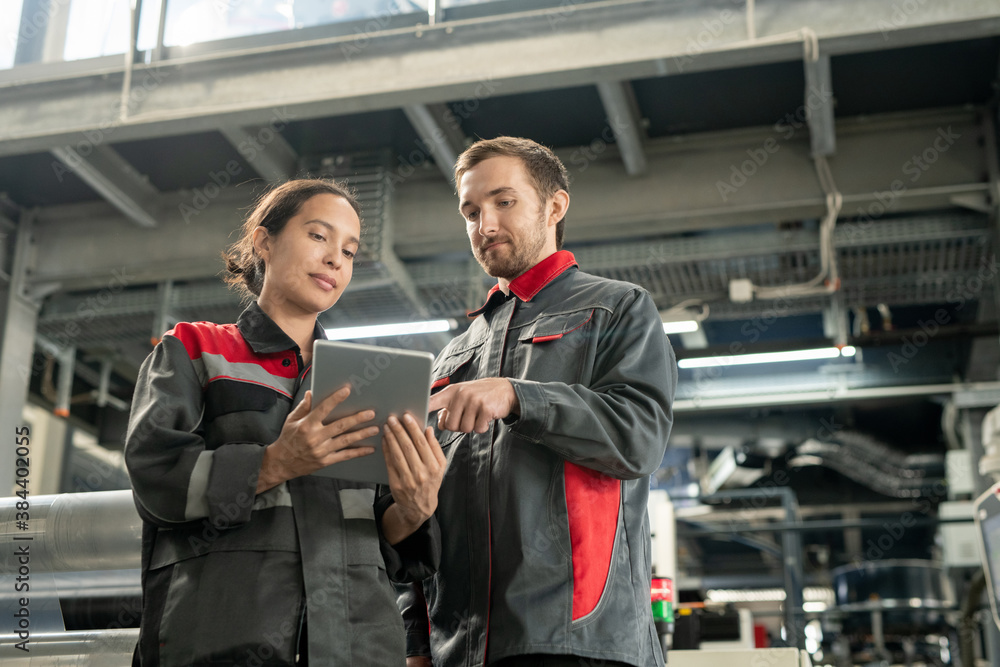 Fototapeta Two young quality control managers of polymer processing factory using tablet