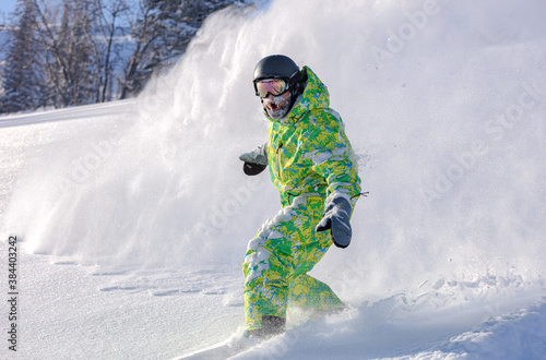 Fotografie, Obraz Extreme snowboarder has fun riding fresh powder snow off piste in white mountains