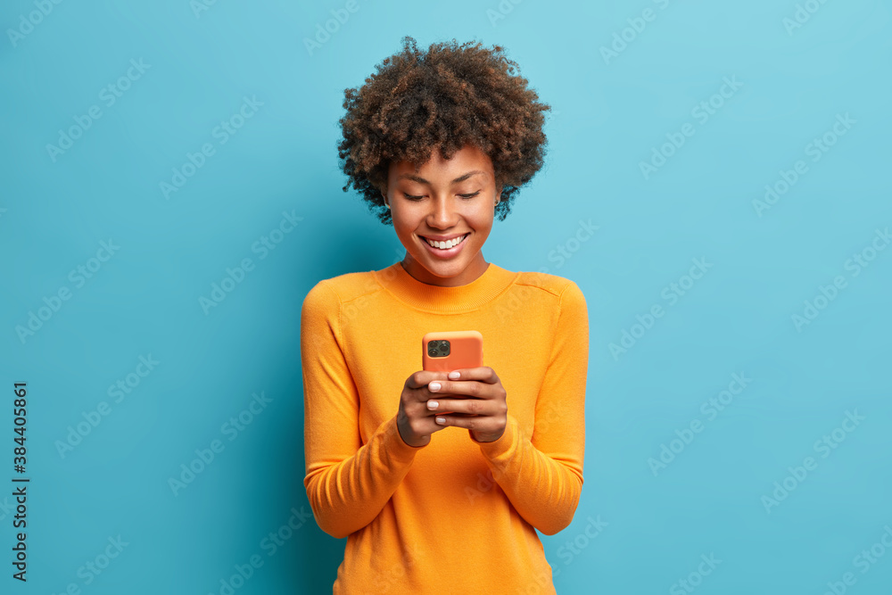 Fototapeta Online lifestyle concept. Cheerful good looking woman with Afro hair sends text messages via mobile phone dressed casually searches gifts for holiday in internet uses smartphone app browses webpage