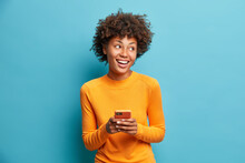 Carefree Pleased Female Student Uses Mobile Phone For Online Distant Education Looks Gladfully Aside And Smiles Broadly Browses Through Internet During Free Time Checks Mailbox Poses Indoor.