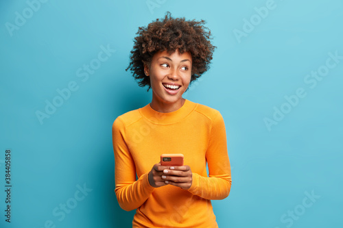 Photo Carefree pleased female student uses mobile phone for online distant education looks gladfully aside and smiles broadly browses through internet during free time checks mailbox poses indoor
