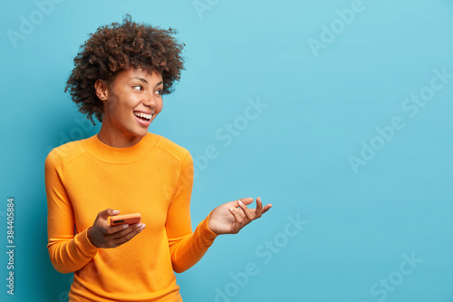 Mobile lifestyle and modern technologies concept. Happy pleased woman raises palm and holds cellphone uses high speed internet for text messaging or video calls isolated on blue studio background