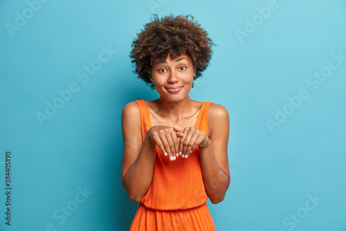 Obraz na plátně Beautiful funny dark skinned Afro American woman makes bunny paws and looks with