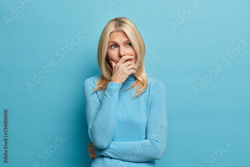 Photo of melancholic thoughtful sad woman thinks about how to solve problem dressed in casual jumper needs to solve problem wears casual turtleneck isolated on blue background Wallpaper Mural