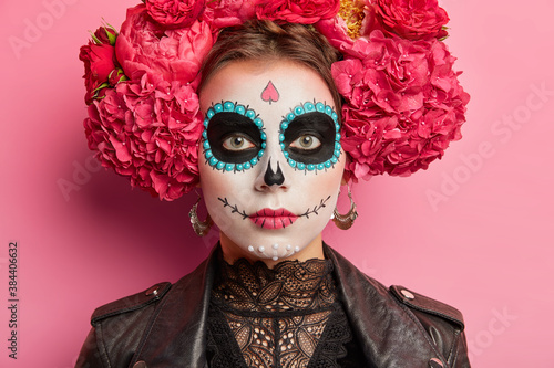Obraz Close up shot of serious woman catrina celebrates halloween or day of death wears peonies wreath and black leather jacket has creative makeup poses against pink background. Horrible spooky female - fototapety do salonu